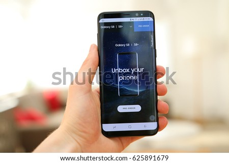 LENDELEDE,BELGIUM - APRIL 22ND 2017: a hand holding a brand new Samsung Galaxy S8 mobile phone with it's publicity on the touch screen. An illustrative editorial image on an interior background