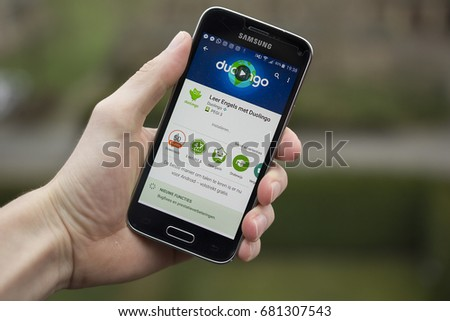 LENDELEDE, BELGIUM - APRIL 21ST 2017:a hand holding a Samsung Galaxy S5 mini mobile phone which displays the Duolingo language app. Illustrative editorial image outside on a green, natural background.