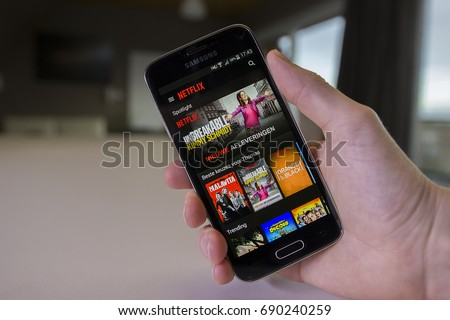 LENDELEDE, BELGIUM - APRIL 20TH 2017: a hand holding a Samsung Galaxy S5 mini mobile phone, displaying the Netflix app. Netflix is an online streaming corporation. An illustrative editorial image.