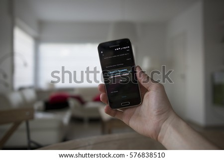 LENDELEDE,BELGIUM - JULY 28TH 2016:a hand holding a Samsung Galaxy S5 mini mobile phone which displays the Shutterstock app with submission info. Illustrative editorial image on an interior background