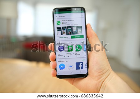 LENDELEDE, BELGIUM-JULY 28TH 2017: a male hand holding a new Samsung Galaxy S8 mobile phone which displays the WhatsApp installation screen. Illustrative editorial image on interior design background.