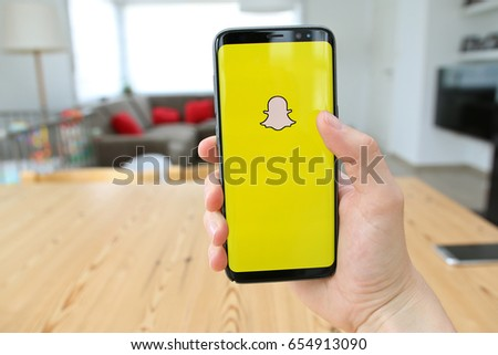 LENDELEDE, BELGIUM - JUNE 6TH 2017:a hand holding a  brand new Samsung Galaxy S8 mobile phone which displays the Snapchat app on the touchscreen. Illustrative editorial image on an interior background