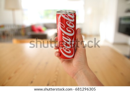 LENDELEDE,BELGIUM-JUNE 20TH 2017:a hand holding a long, red Coca-Cola can. The drink contains 20cl. The internationally known brand name is visible.Illustrative editorial image on interior background.