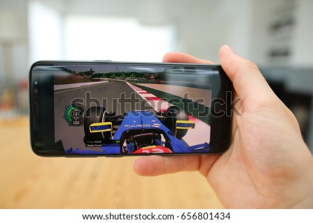 LENDELEDE, BELGIUM- JUNE 6TH 2017:a hand holding a new Samsung Galaxy S8 mobile phone which displays a Formula 1 race app on the touch screen.An illustrative editorial image on an interior background.