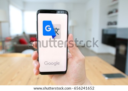 LENDELEDE, BELGIUM - JUNE 6TH 2017:a hand holding a Samsung Galaxy S8 mobile phone which displays the Google Translate app on the touch screen.An illustrative editorial image on an interior background