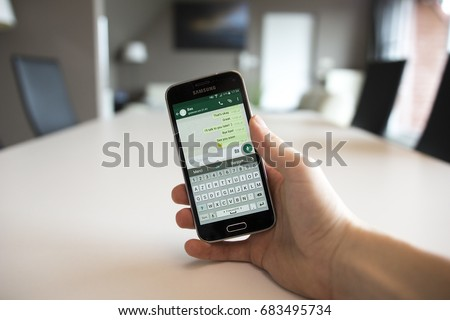 LENDELEDE, BELGIUM - JUNE 28TH 2017: a male hand holding a Samsung Galaxy S5 mini mobile phone which displays the WhatsApp app. An illustrative editorial image on an interior design background.