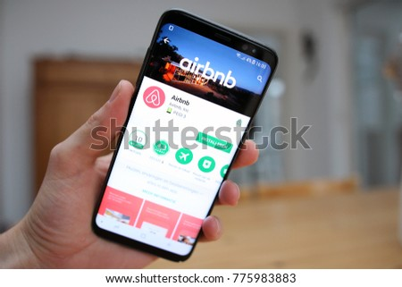 LENDELEDE,BELGIUM-NOVEMBER 29TH 2017:a hand holding a brand new Samsung Galaxy S8 mobile phone which displays the Airbnb app on the touch screen.Illustrative editorial image on an interior background.