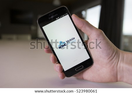 LENDELEDE, BELGIUM - NOVEMBER 28TH 2016: a hand holding a Samsung Galaxy S5 mini mobile phone which displays the Belgian KBC online banking app. Illustrative editorial image on an interior background.