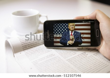 LENDELEDE,BELGIUM-NOVEMBER 8TH 2016:A hand holding a Samsung Galaxy S5 smartphone with Donald Trump on the touch screen.An illustrative editorial image with a newspaper and coffee on the background