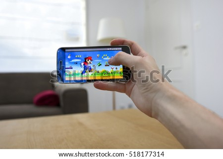 LENDELEDE, BELGIUM - SEPTEMBER 13TH 2016: A hand holding a smartphone with a Super Mario game on the reflective touch screen. An illustrative editorial image on an interior design background.
