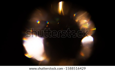 Lens Flare, Abstract Bokeh golden holiday Lights. Leaking Reflection of a Glass, Crystal, Defocused Shining, glowing Colorful rainbow Christmas Light Leaks, Rays on Black Background