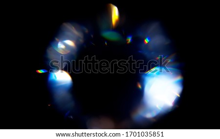 Lens Flare, Abstract Bokeh Lights. Leaking Reflection of a Glass, Diamond,  Crystal. Jewelry. Defocused Shining Colorful rainbow Light Leaks, Rays on Black Background