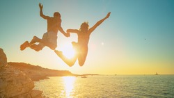 LENS FLARE: Carefree tourists hold hands while jumping into sea at sunset. Cheerful young woman holds her athletic boyfriend's hand as they jump off a cliff and into the cool sea at golden sunset.