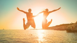 LENS FLARE: Cheerful traveler couple on relaxing summer vacation jumps into the ocean at sunrise. Golden evening sun rays shine on a young man holding girlfriend's hand as they jump in the water.