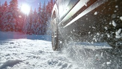 LENS FLARE, CLOSE UP, DOF: Snow glistens in the bright winter sunshine as it flies in the air from the spinning wheels of a powerful car having difficulties getting traction on a snowy and icy road.