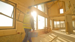 LENS FLARE, CLOSE UP: Golden sunbeams shine on a young worker coming to work in a contemporary prefabricated wooden house. Unrecognizable builder arrives to work carrying his toolbox and ladder.