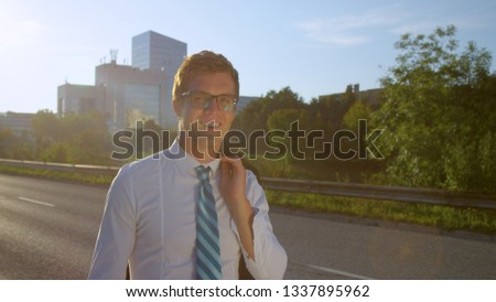 LENS FLARE, CLOSE UP: Young Caucasian man casually walking down the street after a successful meeting at work. Happy businessman wandering around the urban city after work on a sunny summer day.