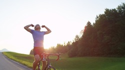 LENS FLARE, COPY SPACE: Athletic sportsman celebrates successful finish of sunny road cycling trial. Pro Caucasian road biker happy to finish challenging training race across scenic summer landscape.