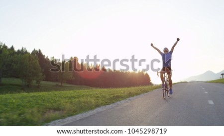 LENS FLARE COPY SPACE Ecstatic pro cyclist looking into the beautiful evening sky and outstretching arms after triumphant bicycle tour. Athletic man on road bike celebrates victory in challenging race
