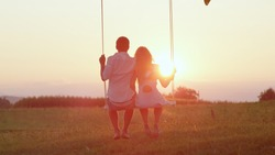 LENS FLARE SILHOUETTE: Unrecognizable couple in love swaying on tree swing at golden summer sunset. Happy man and woman swinging under a tree in sunny evening. Romantic boy and girl embracing on swing