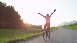 LENS FLARE: Thrilled bicycle rider celebrates win in bike race across countryside by outstretching arms and looking into the golden evening sky. Pro road cyclist rejoicing after completing workout.