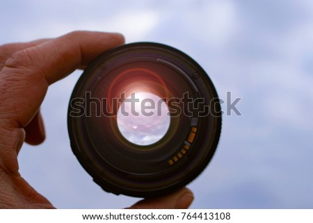 lens in hand against nature background. highlights. #764413108