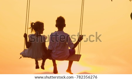 LENSE FLARE Adorable siblings hold hands swaying on late summer evening. Little brother and sister swinging on wood swing in meadow gazing at warm golden sunset. Young love blooming at gold sundown