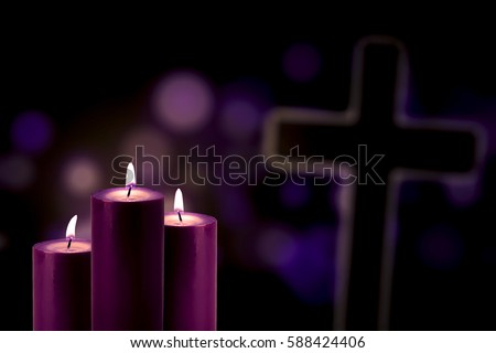 Lent season concept: Picture of three purple candles glowing with a cross symbol and bokeh background