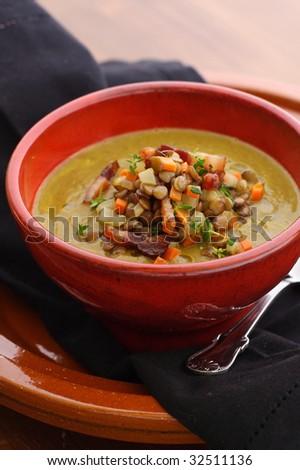 lentil soup with bacon lentil garnish on top