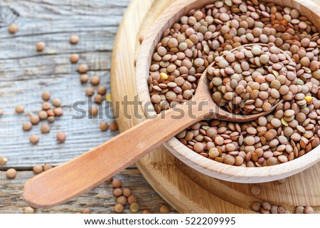 Lentils and spoon in a wooden bowl close up on an old table.