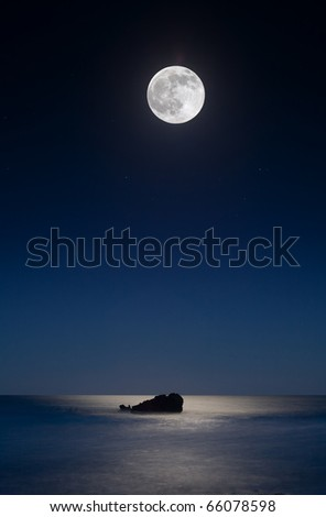 Leo Carillo Beach just outside of Malibu.  The moon shines over a rock in the ocean, reflecting in the water