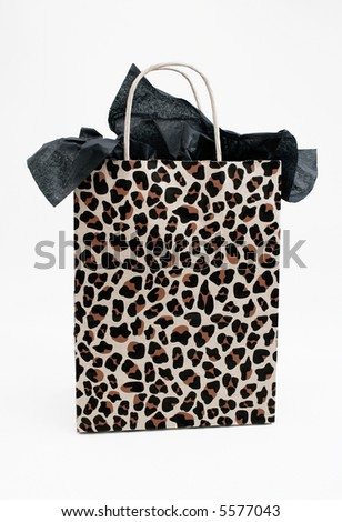 Leopard print gift bag with black tissue paper against a white background.