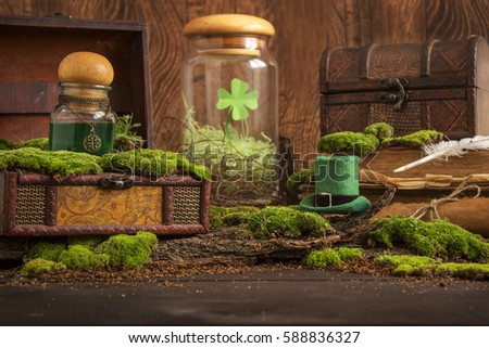 Leprechaun hat with green potion flask on wood table. Old books, bundle, box, chests, moss, shamrock. Saint Patrick's Day concept.