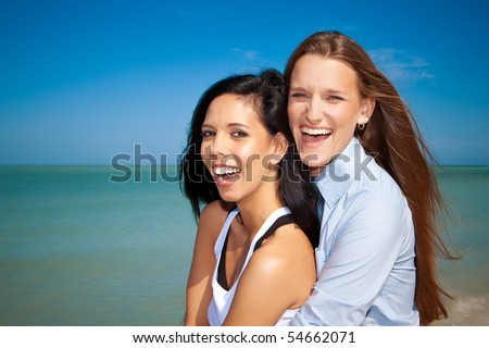 Lesbian couple at the beach laughing