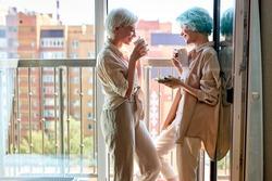 lesbian, couple, breakfast, romance concept. beautiful caucasian lesbian women have breakfast on balcony having talk, enjoying morning together. side view portrait, copy space. people lifestyle