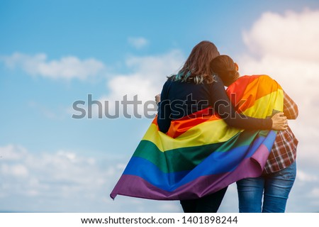 Lesbian couple hugging outdoors. LGBT rainbow flag.