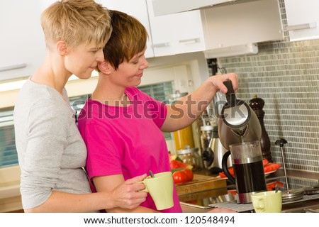 Lesbian couple making coffee with a french press coffee maker
