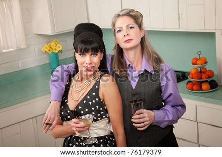 Lesbian couple with drinks and cigar in a retro-style kitchen - stock photo