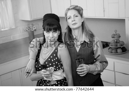 Lesbian couple with drinks and cigar in a retro-style kitchen