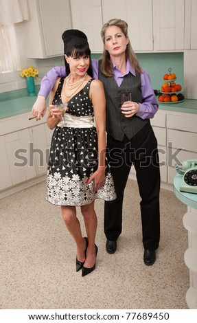 Lesbian couple with drinks and cigar in kitchen
