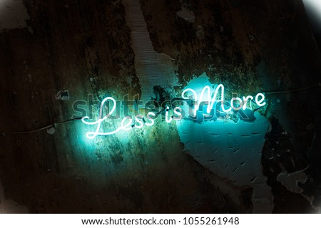 Less is more sign made of green blue led neon tube lights. Dark grunge textured wall. Motivational minimalist quotation