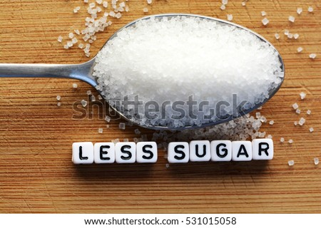 Less sugar text from tiled letter blocks and sugar pile on a spoon suggesting dieting concept