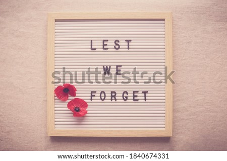 Lest We Forget and red poppy flowers on letter board Stock fotó ©