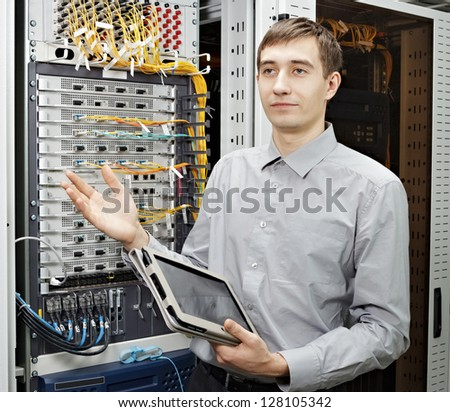 Let me show. The telecom engineer stand in data center and show telecommunication equipment