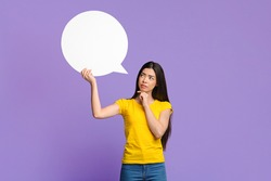 Let Me Think About It. Doubtful Asian Girl Holding And Looking At Empty Speech Bubble, Having Difficult Choice, Standing Over Purple Background