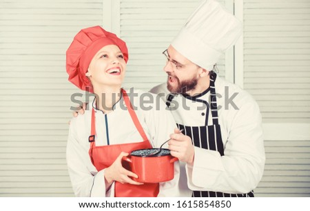 Let my try taste. Couple having fun while whipping cream. Woman and bearded man chef cooking together. Cooking healthy meal. Delicious meal. Baking pie together. Cooking together is more fun.