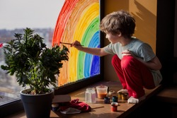 let's all be well. child at home draws a rainbow on the window. Flash mob society community on self-isolation quarantine pandemic coronavirus. Children create artist paints creativity vacation