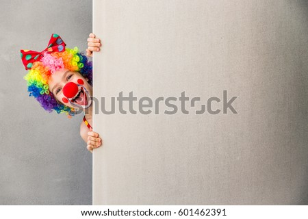 Let's celebrate! Funny kid clown hiding behind cardboard blank. Child holding banner with copy space for your text. 1 April Fool's day concept