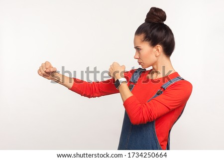 Let's fight! Side view of determined confident girl with hair bun in denim overalls punching, boxing with clenched fists, struggle and self-defence. indoor studio shot isolated on white background Stock photo ©