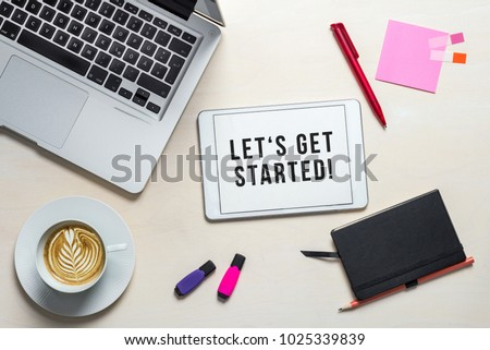 Let's get started writing on tablet screen with laptop, notebook and coffee lying on wooden office desk as flat lay #1025339839